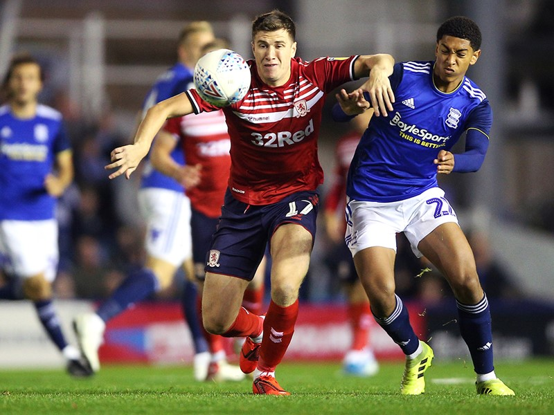 Jude Bellingham challenges Boro's Paddy McNair for the ball.